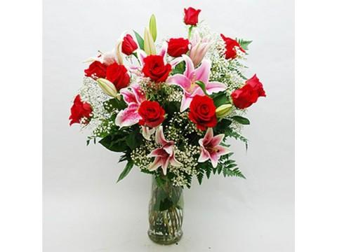 Cam vazoda kırmızı güller ve lilyumlar